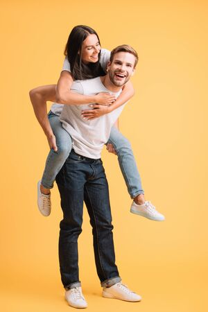 happy man piggybacking his girlfriend, isolated on yellow