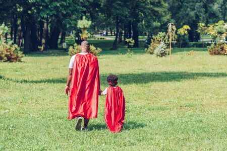 back view of african american father and son holding hands while walking in costumes of superheroes in park Imagens