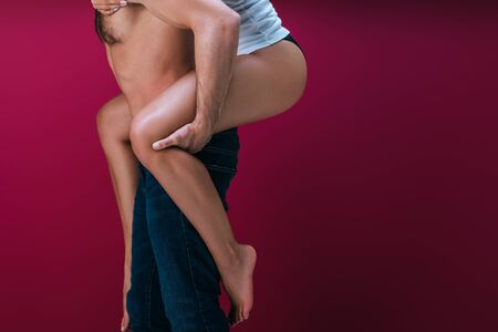 cropped view of shirtless man in denim jeans piggybacking girlfriend in panties on red background