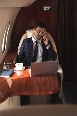 smiling businessman talking on smartphone in plane with laptop during business trip