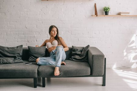 beautiful girl in white bra and jeans sitting on sofa with smartphone