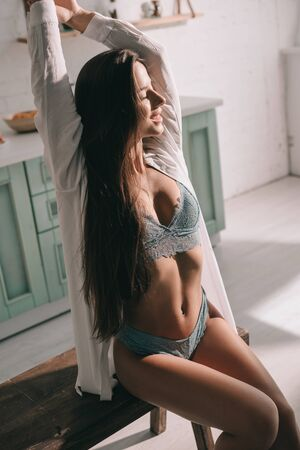 smiling woman with long hair posing in blue lingerie and white shirt in kitchen in the morning Zdjęcie Seryjne