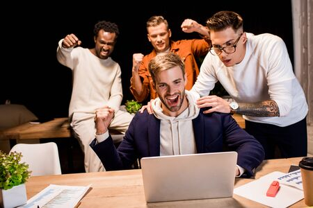 happy multicultural businesspeople showing winner gesture while working at night in office Stok Fotoğraf