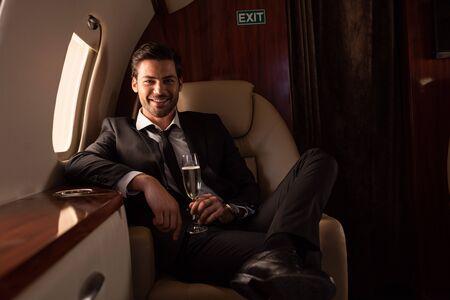 gut aussehender lächelnder Mann, der ein Glas Champagner im Flugzeug hält Standard-Bild