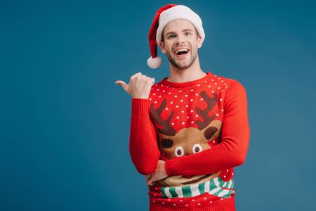 excited handsome man in santa hat and christmas sweater pointing isolated on blue Stock Photo
