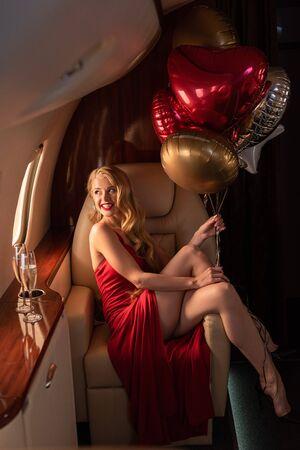 donna felice con champagne e palloncini seduta in aereo Archivio Fotografico