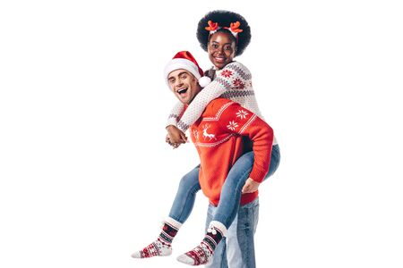 happy interracial couple in santa hat and christmas horns piggybacking, isolated on white