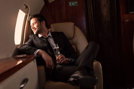 bell'uomo che tiene un bicchiere di champagne in aereo
