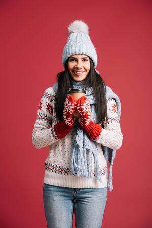 smiling woman in winter hat, scarf and mittens holding coffee to go, isolated on red