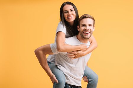 beautiful happy couple piggybacking in white t-shirts, isolated on yellow