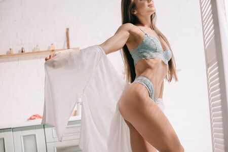 cropped view of smiling sensual girl posing in blue lingerie and white shirt in kitchen Zdjęcie Seryjne