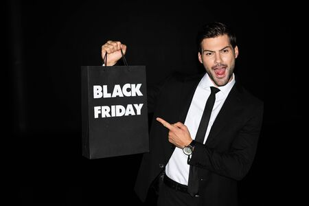 excited man showing shopping bag with black friday sign, isolated on black