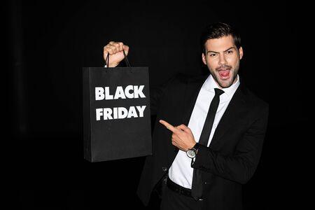 homme excité montrant le panier avec le signe noir de vendredi, d'isolement sur le noir Banque d'images