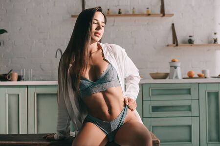 passionate woman posing in blue lingerie and white shirt in kitchen in the morning Zdjęcie Seryjne