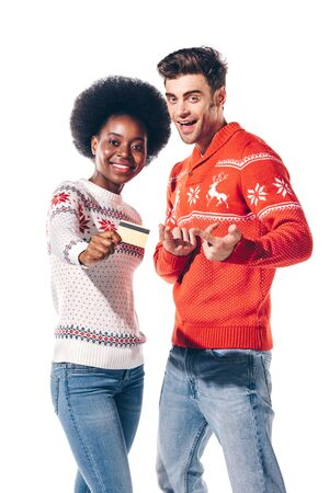 happy multicultural couple in winter sweaters holding credit card, isolated on white