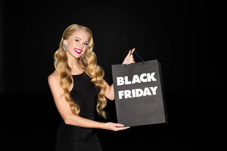 cheerful girl holding shopping bag with black friday sign, isolated on black Фото со стока
