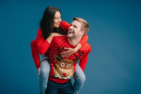 cheerful couple in christmas sweaters piggybacking isolated on blue Stok Fotoğraf