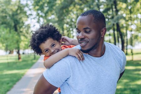 handsome african american man piggybacking cheerful son in park