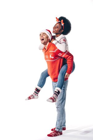 multicultural couple in santa hat and deer horns piggybacking, isolated on white