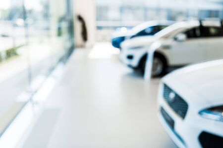 blurred car showroom with new and shiny cars