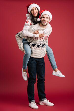 happy boyfriend piggybacking girlfriend in santa hat on christmas on red
