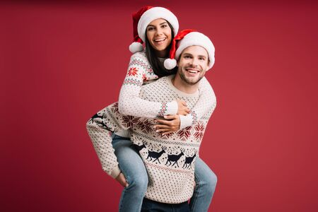 beautiful couple in santa hats and sweaters piggybacking isolated on red