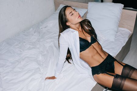 attractive passionate young woman in black lingerie, stockings and white shirt posing on bed 版權商用圖片
