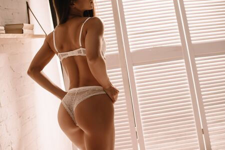 cropped view of sexy girl posing in white lingerie near folding screen 写真素材