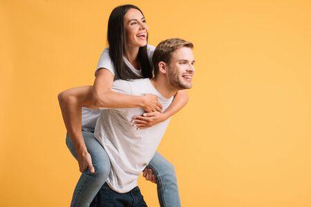 smiling man piggybacking beautiful woman, isolated on yellow Stok Fotoğraf