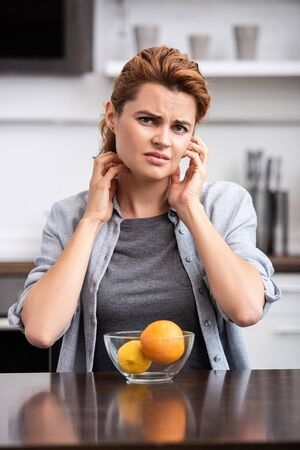 sad woman scratching neck near glass bowl with fruits Stock Photo