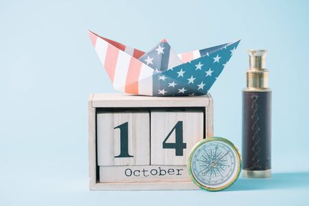paper boat with American flag pattern on wooden calendar with October 14 date near compass and telescope on blue background Banque d'images - 132963060