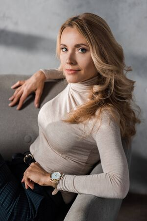 attractive and blonde businesswoman looking at camera and sitting on armchair