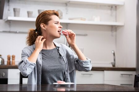 woman with sweet allergy eating pink dessert while scratching neck