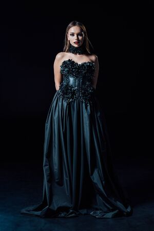 scary vampire girl in black Gothic dress on black background