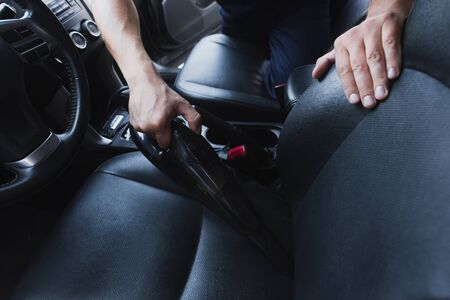 cropped view of car cleaner vacuuming drivers seat in car Stock Photo