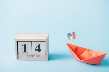 wooden calendar with October 14 date near red paper boar with American flag on blue background Banque d'images - 132958087
