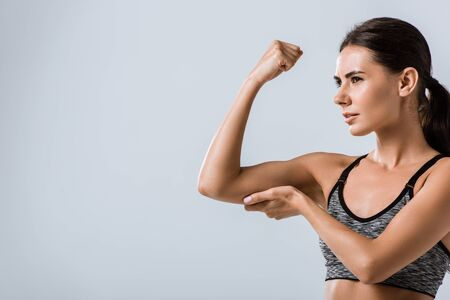 attractive brunette sportswoman touching muscle isolated on grey