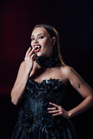 fille vampire effrayante avec des crocs en robe gothique noire isolée sur fond noir Banque d'images