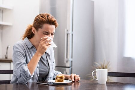 sick woman sneezing in tissue near sweet pancakes at home