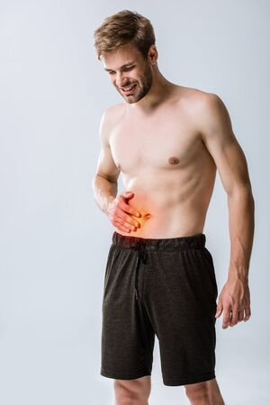 shirtless sportman with abdominal pain isolated on grey