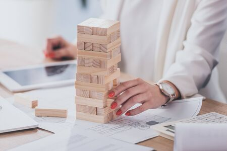 cropped view of businesswoman touching stack of wooden blocks