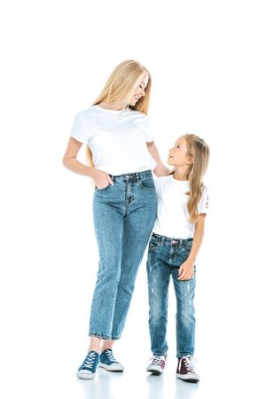 beautiful mother standing with hand in pocket near preteen daughter on white