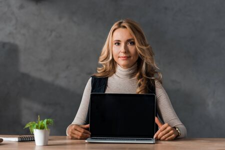 attractive and blonde businesswoman sitting at table with laptop