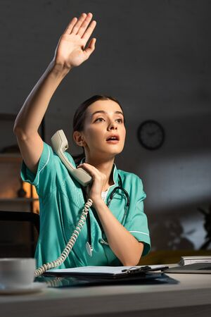 attractive nurse in uniform holding handset and waving during night shift Фото со стока