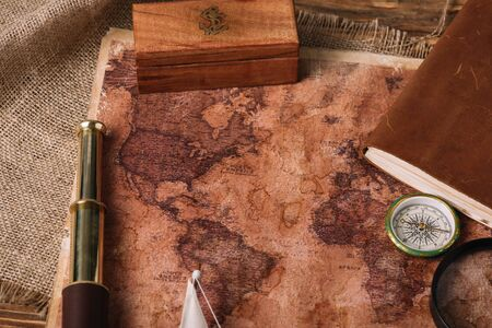 wooden box, telescope, compass and aged world map on hessian Stok Fotoğraf