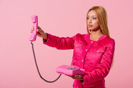 stylish african american woman holding handset isolated on pink, fashion doll concept