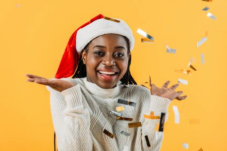 happy African American woman in Santa hat smiling and looking at camera on yellow background with confetti Stock Photo