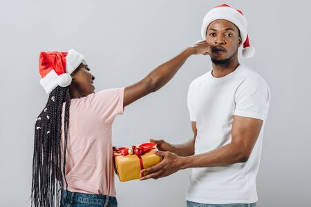 African American woman in Santa hat punching man with gift box isolated on grey