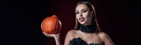 panoramic shot of scary vampire girl with fangs in black gothic dress holding Halloween pumpkin on black background Banque d'images