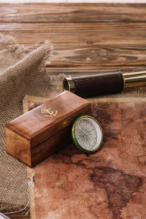box with anchor logo near compass on wooden table with sacking and world map